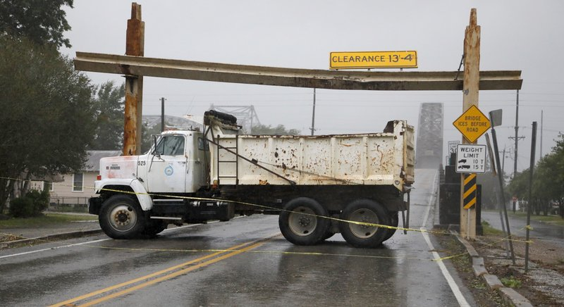 A public works dump truck blocks the Morgan City, La., access to the Long-Allen Bridge in the background, ahead of Tropical Storm Barry, Saturday, July 13, 2019. High buffeting winds are sweeping the truss bridge that crosses over the Atchafalaya River between the communities of Berwick and Morgan City. (AP Photo/Rogelio V. Solis)