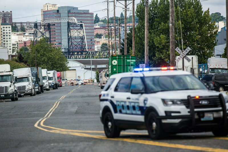 A police officer guards the front of a road block near the Northwest Detention Center, Saturday, July 13, 2019 in Tacoma, Wash. A man armed with a rifle threw incendiary devices at an immigration jail in Washington state early Saturday morning, then was found dead after four police officers arrived and opened fire, authorities said. (Rebekah Welch/The Seattle Times via AP)