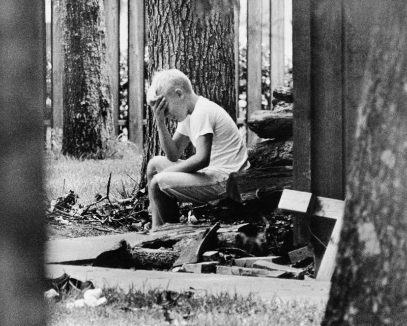 FILE - In this July 20, 1969 file photo, Andy Aldrin, 10, sits on a pile of cordwood in the backyard of his home in Houston while other members of his family listen to the reports of the progress of the Apollo II lunar module carrying his father, Col. Buzz Aldrin and fellow astronaut Neil Armstrong to a landing on the moon. (AP Photo)