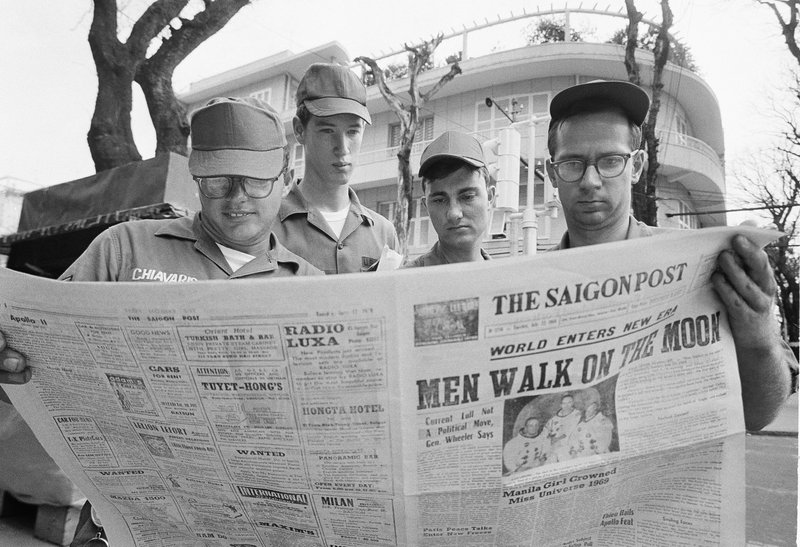 FILE - In this July 21, 1969 file photo, U.S. Air Force Sgt. Michael Chivaris, Clinton, Mass.; Army Spec. 4 Andrew Hutchins, Middlebury, Vt.; Air Force Sgt. John Whalin, Indianapolis, Ind.; and Army Spec. 4 Lloyd Newton, Roseburg, Ore., read a newspaper headlining the Apollo 11 moon landing, in downtown Saigon, Vietnam. (AP Photo/Hugh Van Es)