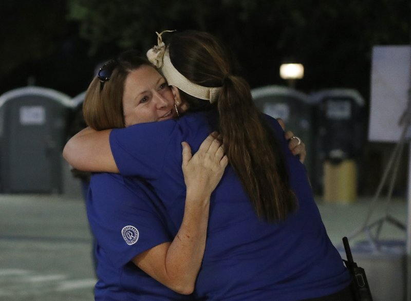 Gilroy Garlic festival volunteer Denise Buessing, left, embraces fellow volunteer Marsha Struzik at a reunification center in a parking lot at Gavilan College following a deadly shooting at the annual food festival in Gilroy, Calif., Sunday, July 28, 2018. (AP Photo/Josie Lepe)