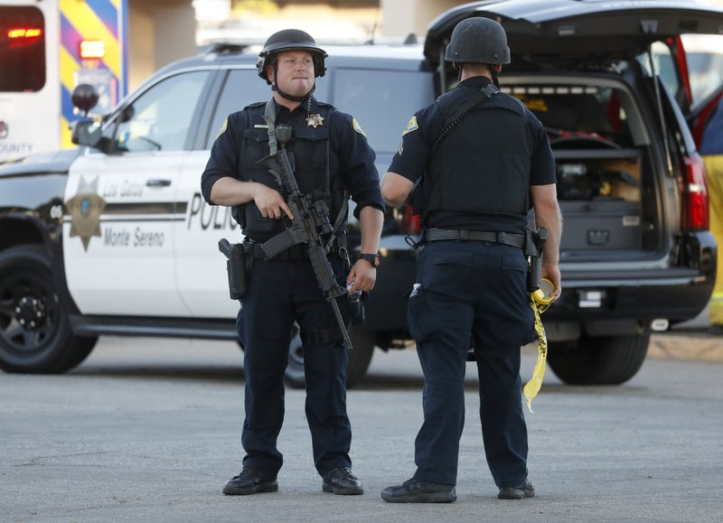 Police stand guard outside Gilroy High School following a deadly shooting at the Gilroy Garlic Festival in Gilroy, Calif., on Sunday, July 28, 2019. (Nhat V. Meyer/San Jose Mercury News via AP)