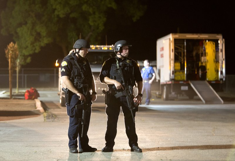 Police officers dressed in SWAT gear stand guard at the first aid center at Gilroy High School following a shooting at the Gilroy Garlic Festival in Gilroy, Calif., on Sunday, July 28, 2019. (AP Photo/David Royal)