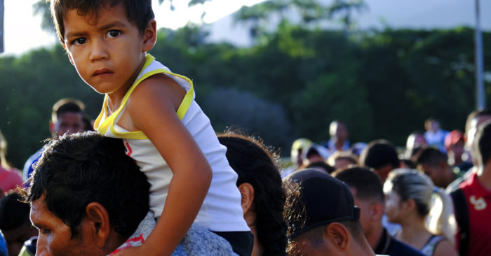A Venezuelan with a child on his shoulders waits to cross the Simón Bolívar international bridge to Cúcuta, Colombia, on Saturday, June 8, 2019. (AP Photo/Ferley Ospina)