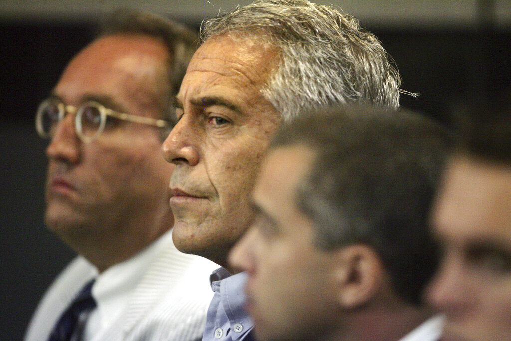 In this archival photograph of July 30, 2008, Jeffrey Epstein, at the center, is shown in custody in West Palm Beach, Florida. (Uma Sanghvi / Palm Beach Post v. AP, Archive)
