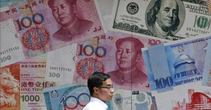 FILE - In this June 10, 2019, file photo, a man walks past a money exchange shop decorated with different banknotes at Central, a business district of Hong Kong. China's yuan fell below the politically sensitive level of seven to the U.S. dollar on Monday, Aug. 5, 2019, possibly adding to trade tension with Washington. (AP Photo/Kin Cheung, File)