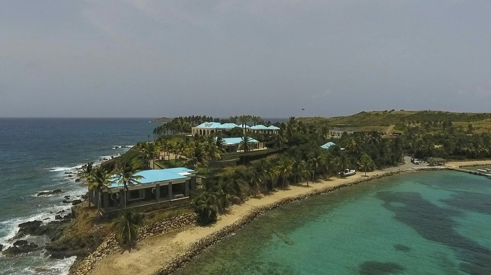 This Tuesday, July 9, 2019 video frame grab shows an aerial view of Little Saint James Island, in the U. S. Virgin Islands, a property purchased by Jeffery Epstein more than two decades ago. Epstein built on the island a stone mansion with cream-colored walls and a bright turquoise roof surrounded by several other structures including the maids' quarters and a massive, square-shaped white building on one end of the island. (AP Photo/Gianfranco Gaglione)