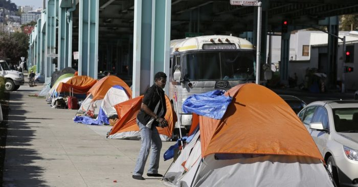 In this Feb. 23, 2016 file photo, a man stands outside his tent on Division Street in San Francisco. (AP/Eric Risberg, File)