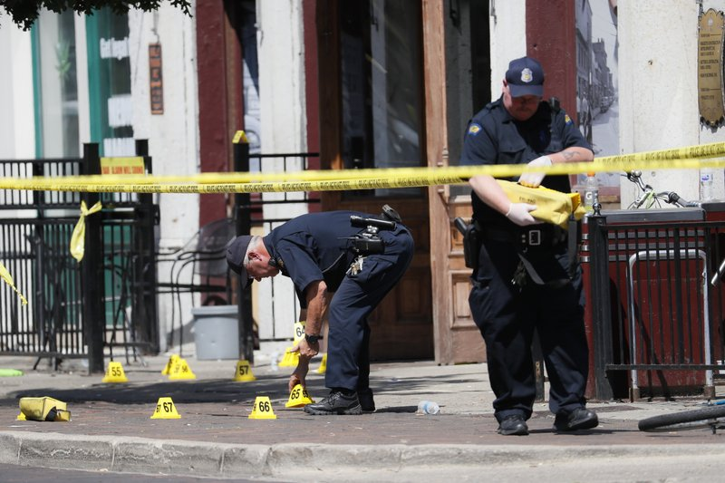 Authorities retrieve evidence markers at the scene of a mass shooting, Sunday, Aug. 4, 2019, in Dayton, Ohio. Multiple people in Ohio have been killed in the second mass shooting in the U.S. in less than 24 hours, and the suspected shooter is also deceased, police said. (AP Photo/John Minchillo)