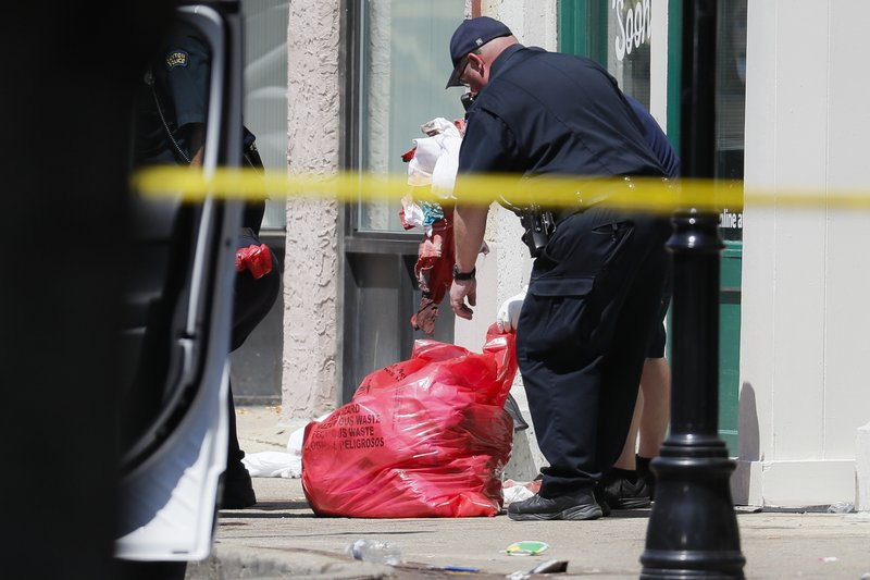 Authorities remove bloody rags and debris at the scene of a mass shooting, Sunday, Aug. 4, 2019, in Dayton, Ohio. Multiple people in Ohio have been killed in the second mass shooting in the U.S. in less than 24 hours, and the suspected shooter is also deceased, police said. (AP Photo/John Minchillo)