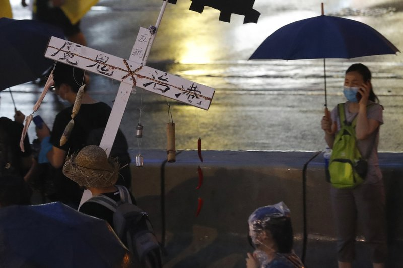 A protester marches with a cross with the words