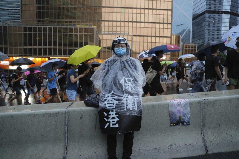 A protester in rain coat wears a sign which reads