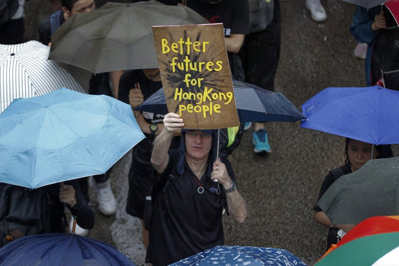 A man displays a placard as protesters gather in Hong Kong Sunday, Aug. 18, 2019. Heavy rain fell on tens of thousands of umbrella-ready protesters as they started marching from a packed park in central Hong Kong, where mass pro-democracy demonstrations have become a regular weekend activity. (AP Photo/Vincent Thian)