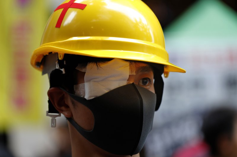 A protester, wearing an eye patches to show solidarity to a woman reportedly injured in the eye by a beanbag fired by police, takes part in a rally in Hong Kong on Sunday, Aug. 18, 2019. A spokesman for China's ceremonial legislature condemned statements from U.S. lawmakers supportive of Hong Kong's pro-democracy movement, as more protests were planned Sunday following a day of dueling rallies that highlighted the political divide in the Chinese territory. (AP Photo/Vincent Thian)