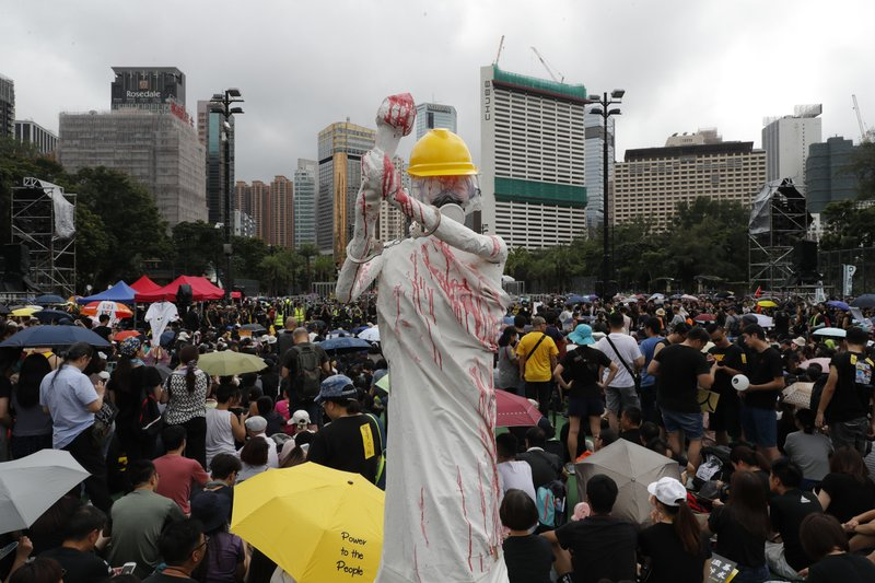 A replica of the Goddess of Democracy is displayed, wearing hard hat, gas mask, handcuffs and covered in a red liquid during a protest rally in Hong Kong on Sunday, Aug. 18, 2019. A spokesman for China's ceremonial legislature condemned statements from U.S. lawmakers supportive of Hong Kong's pro-democracy movement, as more protests were planned Sunday following a day of dueling rallies that highlighted the political divide in the Chinese territory. (AP Photo/Vincent Thian)