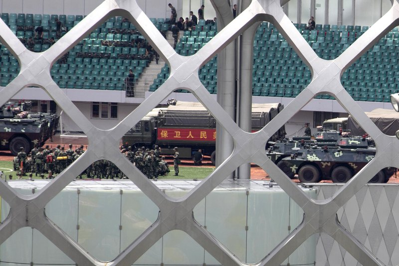 Chinese paramilitary policemen go through drills near the slogan for