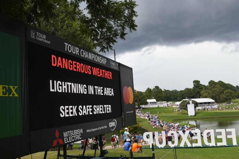 A sign warns of inclement weather as fans come off the course after a delay was called during the third round of the Tour Championship golf tournament Saturday, Aug. 24, 2019, in Atlanta. (AP Photo/John Amis)