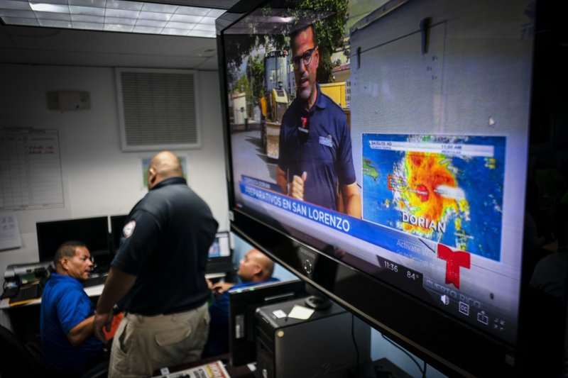 Emergency Center personnel stand next to a tv screen showing a meteorological image of the tropical storm Dorian, as they await its arrival, in Ceiba, Puerto Rico, Wednesday, Aug. 28, 2019. Puerto Rico is facing its first major test of emergency preparedness since the 2017 devastation of Hurricane Maria as Tropical Storm Dorian nears the U.S. territory at near-hurricane force.  (AP Photo/Ramon Espinosa)