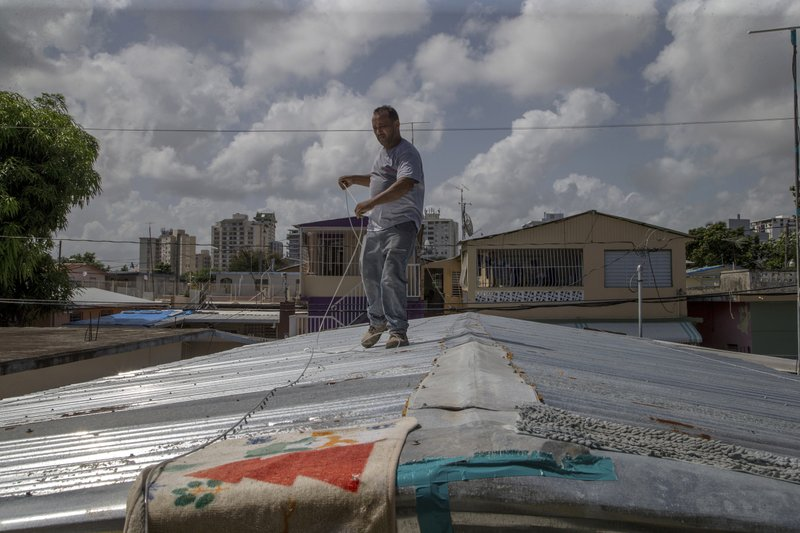 Jorge Ortiz works to tie down his roof as he prepares for the arrival of Tropical Storm Dorian, in the Martín Peña neighborhood of San Juan, Puerto Rico, Tuesday, Aug. 27, 2019. The 50-year-old construction worker was taking no chances as Dorian approached Puerto Rico on Tuesday and threatened to brush past the island's southwest coast at near-hurricane strength. (AP Photo/Gianfranco Gaglione)