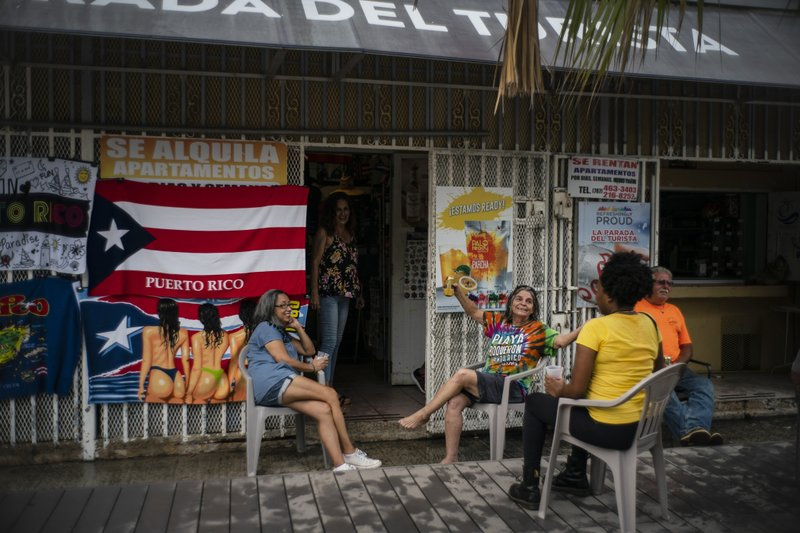 People drink beer on a patio before the arrival of Tropical Storm Dorian in Boqueron, Puerto Rico, Tuesday, Aug. 27, 2019. (AP Photo/Ramon Espinosa)