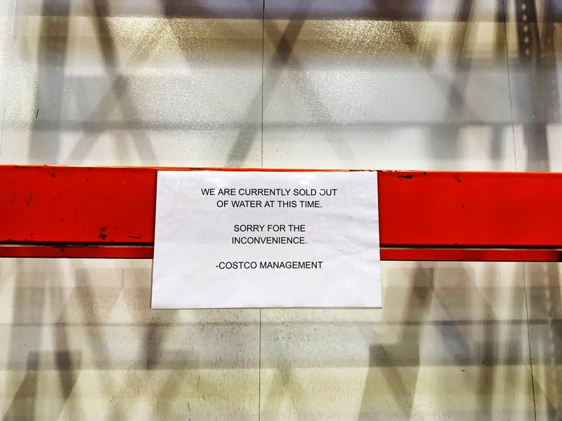 Empty shelves are seen with a sign at Costco stating that the retailer is currently sold out of water ahead of Hurricane Dorian on Thursday, Aug. 29, 2019, in Davie, Fla. (AP Photo/Brynn Anderson)