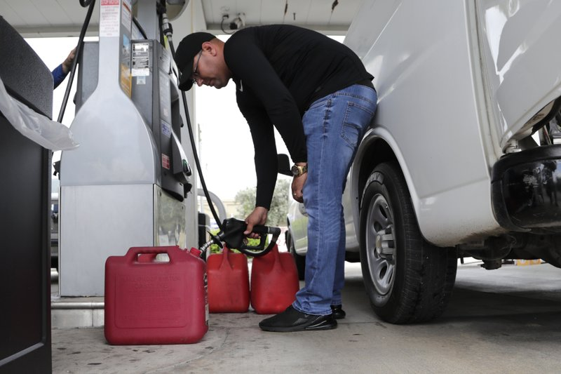 Arian Britto fills containers with gasoline at BJ's Wholesale Club in preparation for Hurricane Dorian, Thursday, Aug. 29, 2019, in Hialeah, Fla. Hurricane Dorian is heading towards Florida for a possible direct hit on the state over Labor Day. (AP Photo/Lynne Sladky)