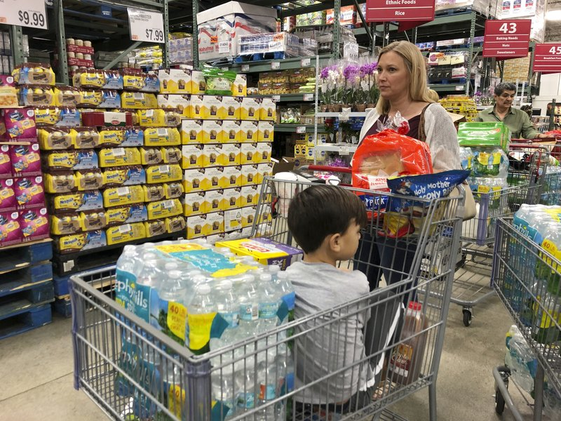 Tiffany Miranda of Miami Springs stands in line with supplies at a BJ's Wholesale Club Thursday, Aug. 29, 2019, in Hialeah, Fla. Miranda has been through five hurricanes and has never evacuated. She says,