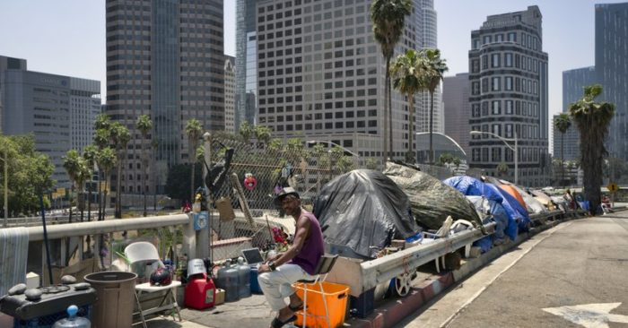 In this May 10, 2018 file photo a homeless man sits at his street side tent along the Interstate 110 freeway along downtown Los Angeles' skyline. (AP/Richard Vogel, file)