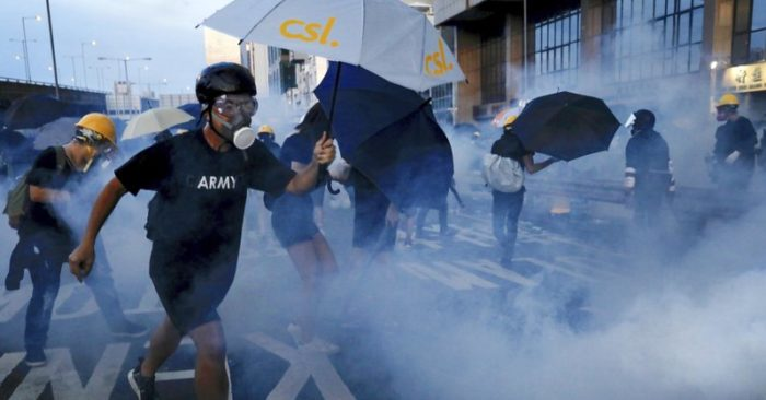 Protesters react from tear gas as they face off with riot policemen on a streets in Hong Kong, Sunday, July 28, 2019. Police launched tear gas at protesters in Hong Kong on Sunday for the second night in a row in another escalation of weeks-long anti-government and pro-democracy protests in the semi-autonomous Chinese territory. (AP Photo/Vincent Yu)
