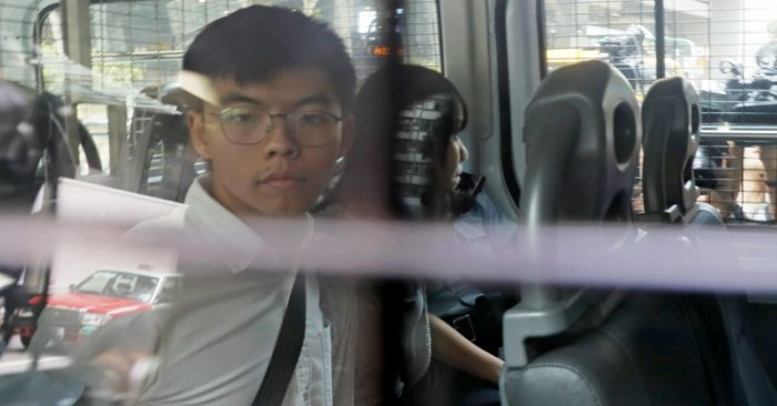 Pro-democracy activists Joshua Wong, left, and Agnes Chow, are escorted in a police van at a district court in Hong Kong on Friday, August 30, 2019. (Photo AP / Kin Cheung)