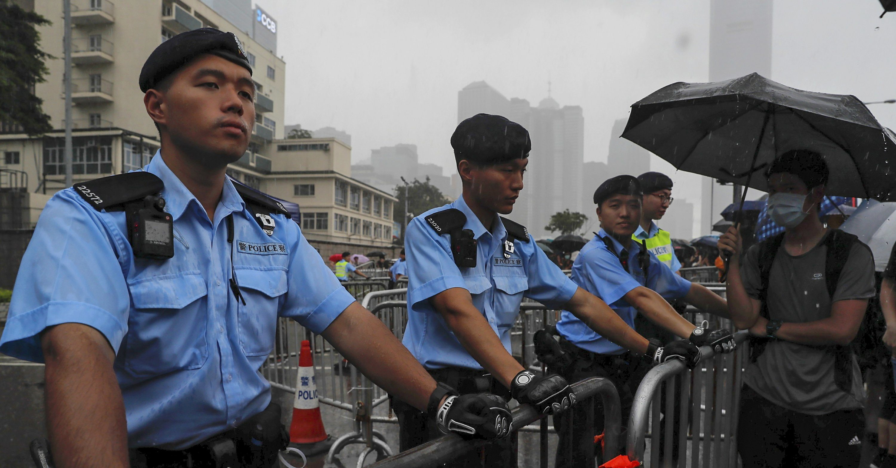 Policemen stand guard in the rain as protesters gather near the Legislative Council continuing protest against the unpopular extradition bill in Hong Kong Monday