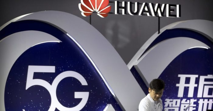 FILE- In this photograph of September 26, 2018, a person uses a laptop in an exhibition of 5G wireless technology of the Chinese company Huawei, in Beijing. (AP Photo / Mark Schiefelbein, File)