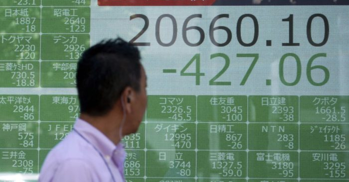 A man walks past an electronic stock board showing Japan's Nikkei 225 index at a securities firm in Tokyo Monday, Aug. 5, 2019. Asian stock markets fell for a third day Monday after China allowed its yuan to sink to its lowest level this year following President Donald Trump's latest tariff threat.(AP Photo/Eugene Hoshiko)