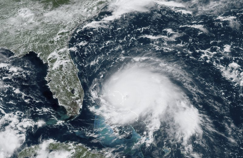 This GOES-16 satellite image taken Sunday, Sept. 1, 2019, at 17:00 UTC and provided by National Oceanic and Atmospheric Administration (NOAA), shows Hurricane Dorian, right, churning over the Atlantic Ocean. Hurricane Dorian struck the northern Bahamas on Sunday as a catastrophic Category 5 storm, its 185 mph winds ripping off roofs and tearing down power lines as hundreds hunkered in schools, churches and other shelters. (NOAA via AP)