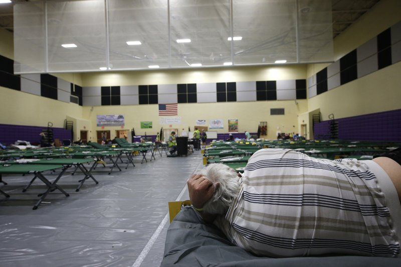 An evacuee lies on a cot at an evacuation shelter for people with special needs, in preparation for Hurricane Dorian, at Dr. David L. Anderson Middle School in Stuart, Fla., Sunday, Sept. 1, 2019. Some coastal areas are under a mandatory evacuation since the path of the storm is still uncertain. (AP Photo/Gerald Herbert)