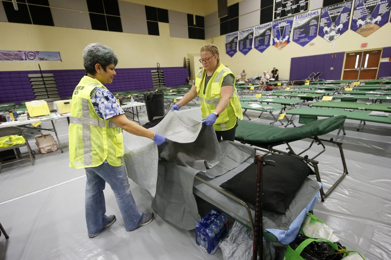 Florida Department of Health staffers set up beds at an evacuation shelter for people with special needs, in preparation for Hurricane Dorian, at Dr. David L. Anderson Middle School in Stuart, Fla., Sunday, Sept. 1, 2019. Some coastal areas are under a mandatory evacuation since the path of the storm is still uncertain. (AP Photo/Gerald Herbert)