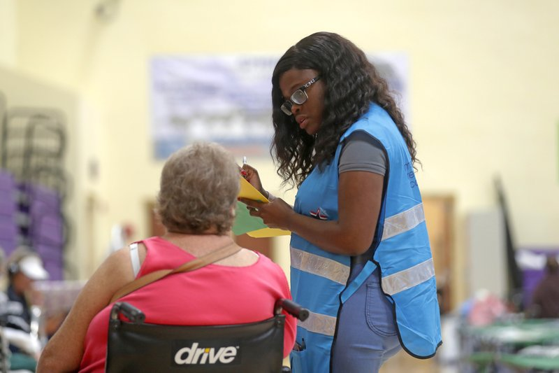 Karen Alexis, a Florida Department of Heath staffer, gets information from an evacuee, at an evacuation shelter for people with special needs, in preparation for Hurricane Dorian, at Dr. David L. Anderson Middle School in Stuart, Fla., Sunday, Sept. 1, 2019. Some coastal areas are under a mandatory evacuation since the path of the storm is still uncertain. (AP Photo/Gerald Herbert)