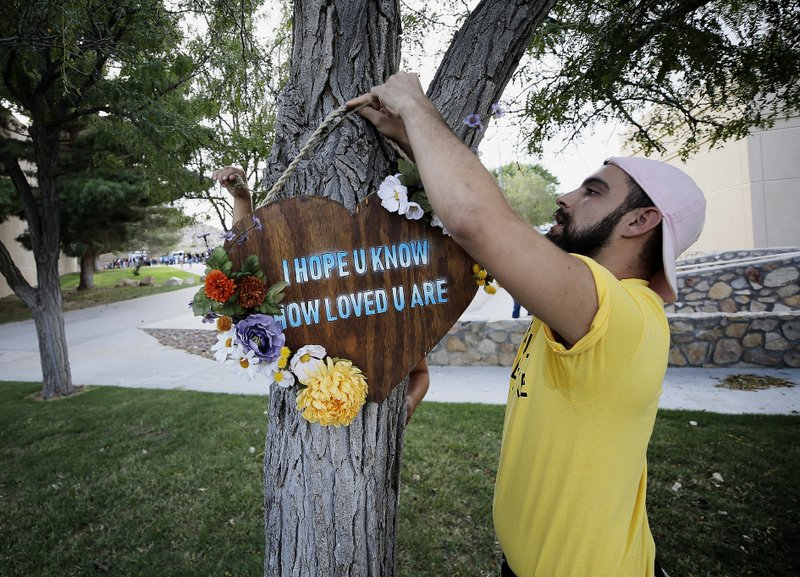 Los Angeles-based artists Noah Reich, right, and David Maldonado, behind the tree, hang a heart-shaped sign on a tree outside a benefit concert by Khalid for the Walmart shooting victims in El Paso, Texas, Sunday, Sept. 1, 2019. (Mark Lambie/The El Paso Times via AP)