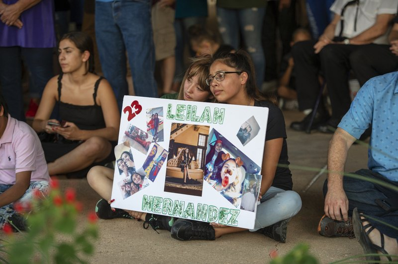 Celeste Lujan, left, and Yasmin Natera hold a sign in honor of Leilah Hernandez during a vigil for victims of the shooting spree the day before, Sunday, Sept. 1, 2019, at the University of Texas of the Permian Basin quad, in Odessa, Texas. (Jacy Lewis/Reporter-Telegram via AP)
