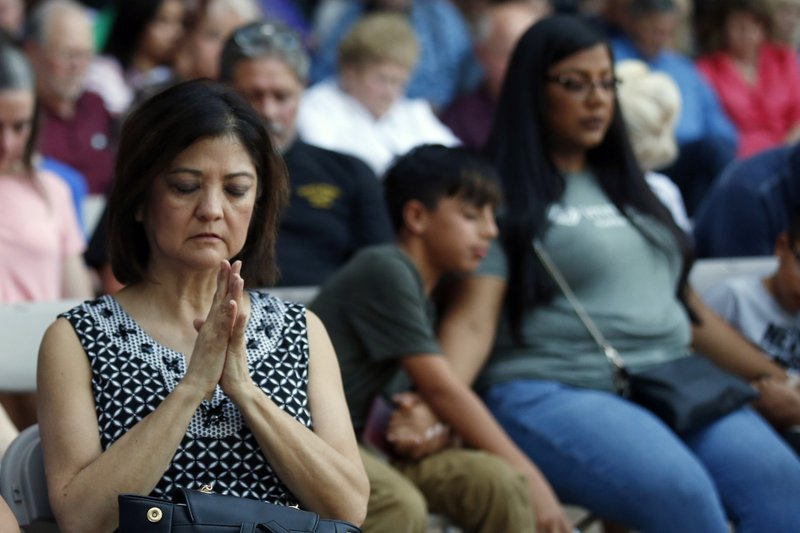 Mira Marquez, of Midland, Texas, folds her hands in prayer during a prayer service, Sunday, Sept. 1, 2019, in Odessa, Texas, for the victims of a shooting spree the day before. (AP Photo/Sue Ogrocki)