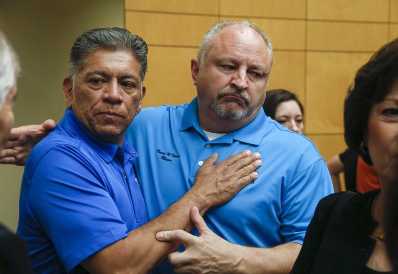 Midland, Texas, Mayor Jerry Morales, left, embraces Odessa, Texas, Mayor David Turner following a news conference at the University of Texas Permian Basin in Odessa, Texas, Sunday, Sept. 1, 2019. (Ryan Michalesko/The Dallas Morning News via AP)