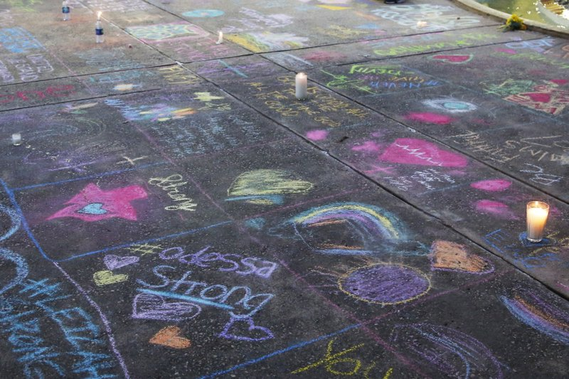 A sidewalk is filled with chalk messages following a prayer service, Sunday, Sept. 1, 2019, in Odessa, Texas, for the victims of a shooting spree the day before. (AP Photo/Sue Ogrocki)