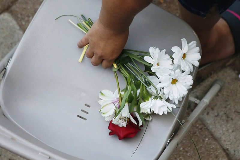 A woman reaches for a bunch of flowers during a memorial service for the victims of Saturday's shootings at a memorial service Sunday, Sept. 1, 2019, in Odessa, Texas. (AP Photo/Sue Ogrocki)
