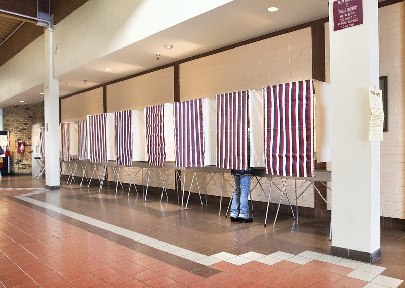 FILE - In this Aug. 21, 2018 file photo, a voter uses a polling booth during primary election day at Ketchikan Precinct 2 in the Plaza building in Ketchikan, Alaska. The Alaska Republican Party has canceled holding a presidential primary in 2020. In a statement Saturday, Sept. 21, 2019, the party's State Central Committee passed a rule saying a primary