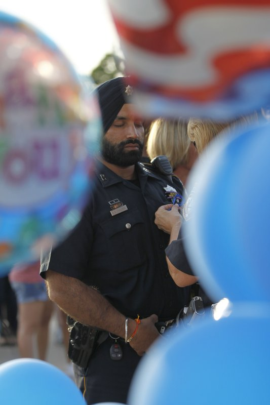 In this Aug. 29, 2015, photo, Harris County Sheriffs deputy Sandeep Dhaliwal gets a blue ribbon pinned to him during a vigil at the Chevron station in Houston, where Harris County deputy Darren Goforth was shot and killed previous night while he was refueling his vehicle. Dhaliwal was shot and killed while making a traffic stop Friday, Sept. 27, 2019, near Houston. (Karen Warren/Houston Chronicle via AP)