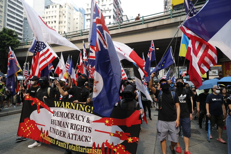 Protestors wave flags of various countries including the U.S. in Hong Kong, Sunday, Sept. 29, 2019. Riot police fired tear gas Sunday after a large crowd of protesters at a Hong Kong shopping district ignored warnings to disperse in a second straight day of clashes, sparking fears of more violence ahead of China's National Day. (AP Photo/Vincent Thian)