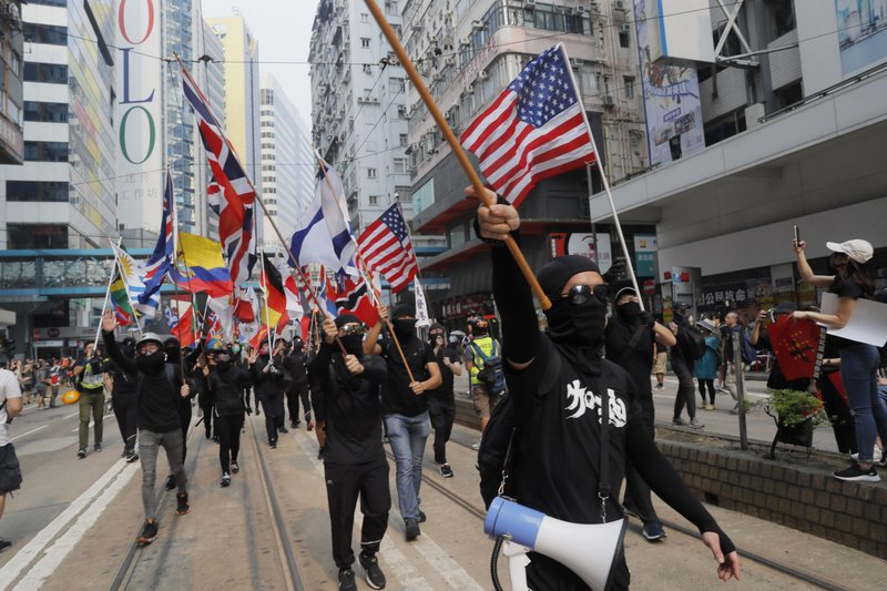Protesters march with flags from various countries in Hong Kong on Sunday, Sept. 29, 2019. Sunday's gathering of protesters, a continuation of monthslong protests for greater democracy, is part of global
