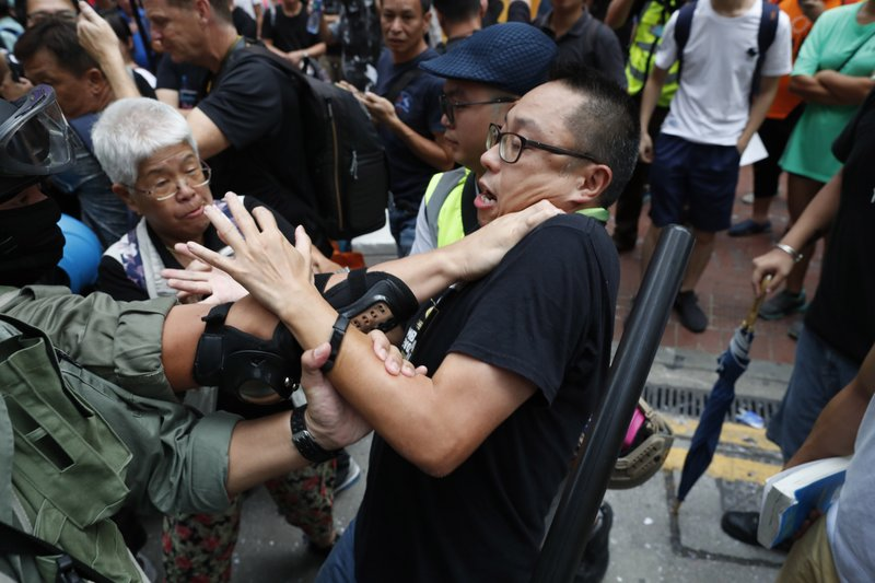 A protestor confronts police and gets detained in Hong Kong, Sunday, Sept. 29, 2019. Police on Saturday fired tear gas and water cannons after protesters threw bricks and firebombs at government buildings following a massive rally in downtown Hong Kong. The clashes were part of a familiar cycle since protests began in June over a now-shelved extradition bill and have since snowballed into an anti-China movement with demands for democratic reforms. (AP Photo/Gemunu Amarasinghe)
