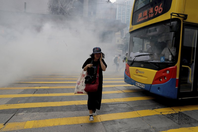 A woman walks near tear gas during a protest in Hong Kong on Sunday, Sept. 29, 2019. Sunday's gathering of protesters, a continuation of monthslong protests for greater democracy, is part of global
