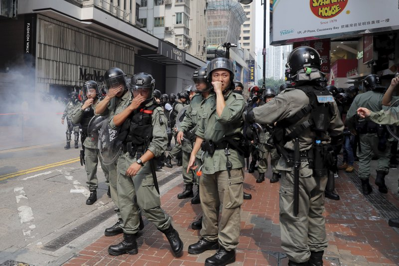 Hong Kong police react to tear gas during a protest in Hong Kong on Sunday, Sept. 29, 2019. Sunday's gathering of protesters, a continuation of monthslong protests for greater democracy, is part of global